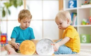 Two Kids playing with moon lamps